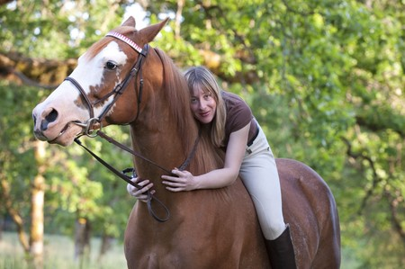 Bareback pretty woman rider embracing her horse