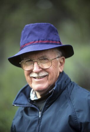 Jaunty older man in blue hat and with a mustache.