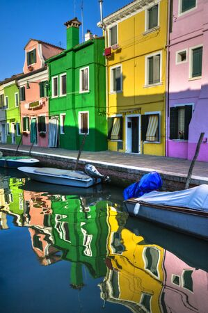 burano: Houses and boats and their reflections in the canals of Burano, Italy