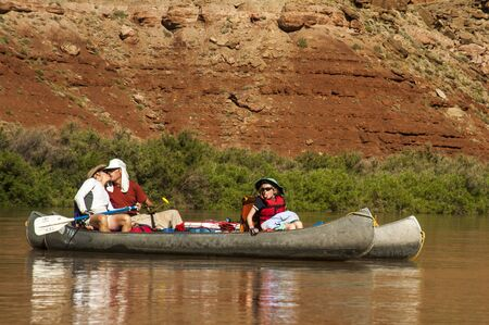 Husband and wife kissing in canoes, while daughter sticks out tongue photo