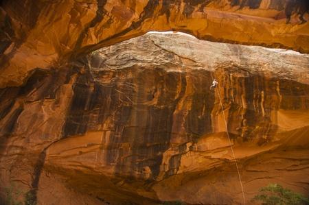 Man rappelling down orange rocks in desert Southwest Archivio Fotografico