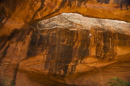 Man rappelling down orange rocks in desert Southwest Stock Photo