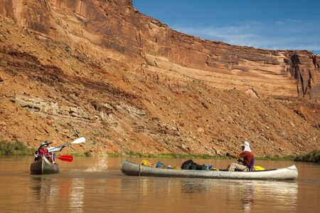Family splashing each other with paddles while in canoes on Green River, Utah photo