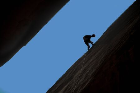 Silhouette of rock climber rappelling a crack with blue sky behind. photo