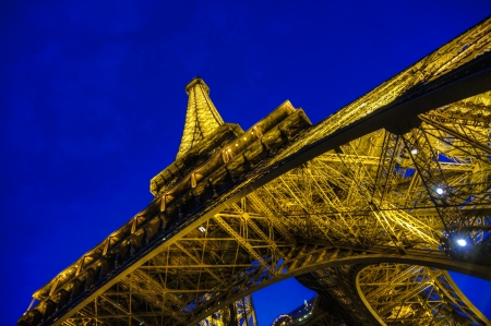 Looking up at the Eiffel Tower from below at night