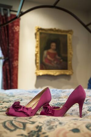 bedspread: Sexy red high heels resting on an antique bed