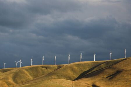Wind turbines below a stormy sky in Washington State photo
