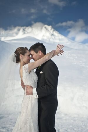 couple winter: Bride and groom in winter snow on mountain
