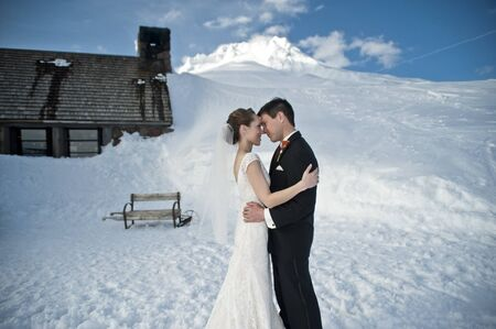 Bride and groom in winter snow on mountain