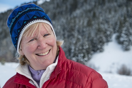 Middle aged woman smiling in winter snow photo