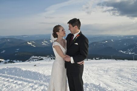 Bride and groom in winter snow on mountain photo