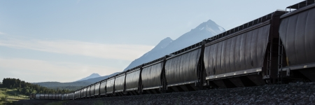 Freight train with hopper cars beneath mountains