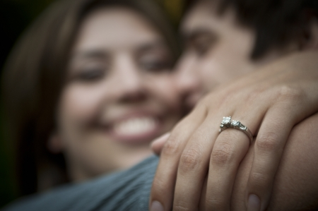 Engaged couple embracing, focus on ring Stock Photo - 18063387