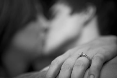 Engaged couple embracing, focus on ring