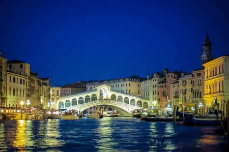 Rialto bridge glowing bright at night, Venice, Italy
