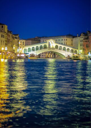 Rialto bridge glowing bright at night, Venice, Italy