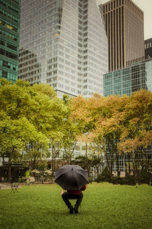Man with umbrella in Bryant Park, among skyscrapers, New York City