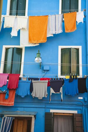 Laundry drying outside a blue house in Burano, Italy