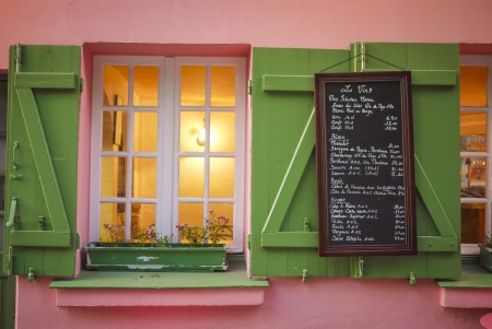Pink cafe, green shutters and menu board, Paris, France
