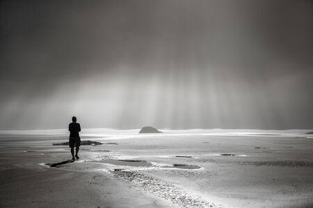 霧のビーチに太陽光線に向かって歩いて一人 写真素材