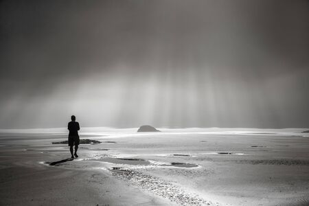 One person walking toward sunbeams on misty beach