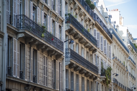 awnings: Apartment building with wrought iron balconies in Paris, France Stock Photo