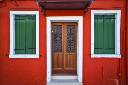Front of a red house with green shuttered windows in Burano, Italy photo