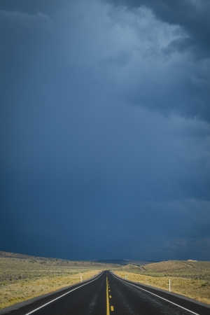 Dark clouds threatening a rain storm above desert\ highway