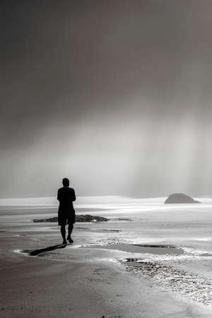 One person walking toward sunbeams on misty beach photo