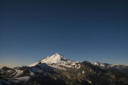 cascade range: Snowcapped Mount Baker, under sky full of stars, lit by the full moon Stock Photo