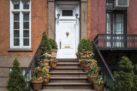 multifamily: Entrance to Greenwich Village apartment with flowerpots on steps, New York City Stock Photo