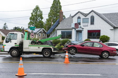 fender bender: Tow truck hauling away a passenger car after a traffic accident caused by wet streets Editorial