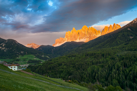 Sunset clouds above Funes Valley in Dolomite mountains in northern Italy