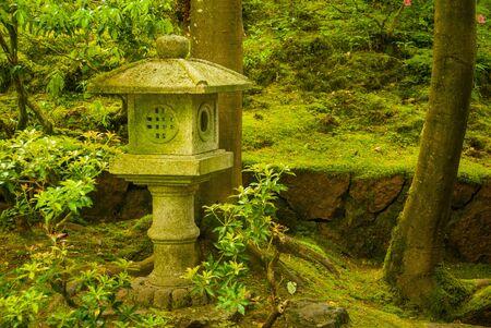 Shinto shrine in mossy green Japanese garden Stock Photo