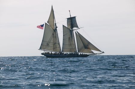 Tall Ship under sail with the shore in the background photo