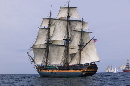 HMS Surprise Sailing Ship at Sea under full sail with tall ships in the background.
