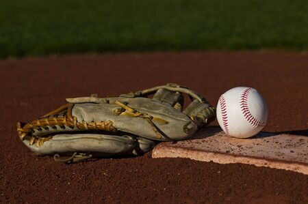 Baseball in a mit sitting on the grass and dirt of a diamond Stok Fotoğraf