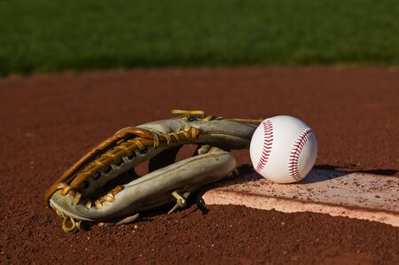 Baseball in a mit sitting on the grass and dirt of a diamond Stok Fotoğraf - 3951137