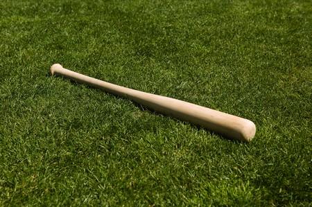 Baseball bat on the green grass of a ball field Stok Fotoğraf