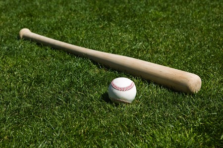 Baseball and bat on the green grass of a ball field