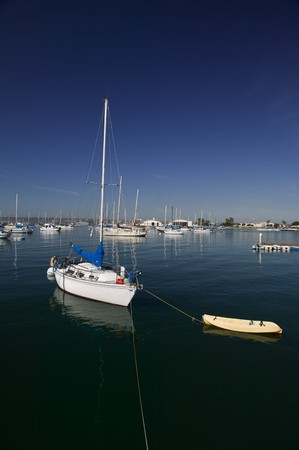 Sail boat moored in a harbor on a clear blue day Stock Photo