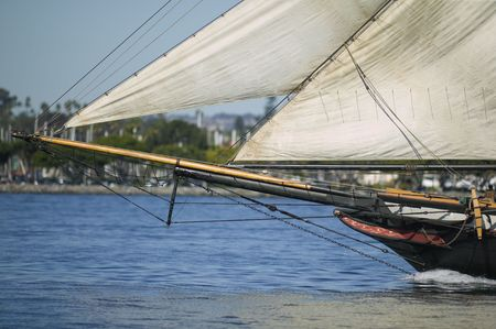 A close up with a telephoto lens of the bow sprint of a vintage sailing ship at sea with all the sails out.