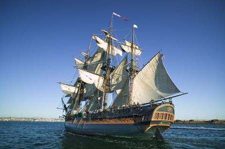 Tall Sailing Ship at Sea under full sail with tall ships in the background.