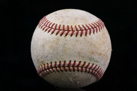 A worn baseball on a black background