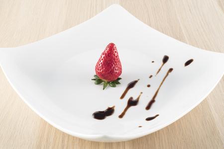 balsamic: Strawberry with balsamic vinegar on white plate