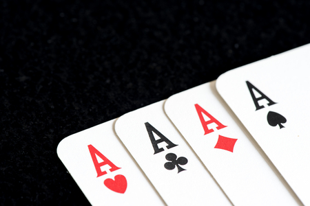 four of a kind: Playing card on black table, four a kind aces Stock Photo