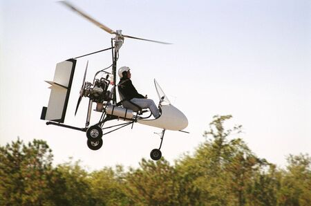 Gyrocopter in flight (face intentionally obscurred)