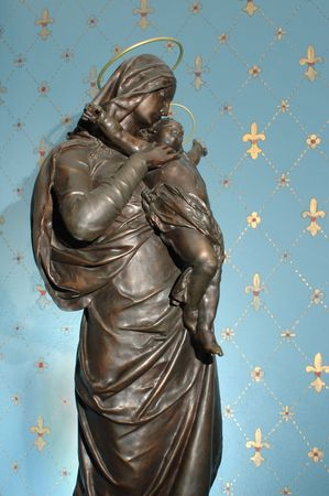 Bronze sculpture of Virgin and Child by Gustave Dore (1833-1883), exhibited in Paris in 1880,  against a painted plaster/stucco wall with some plaster background texture visible.