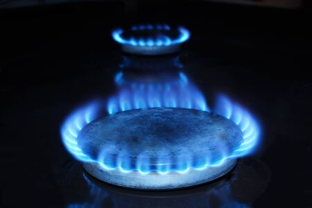 natural gas prices: Fire of natural gas at kitchen stove in the dark. Stock Photo