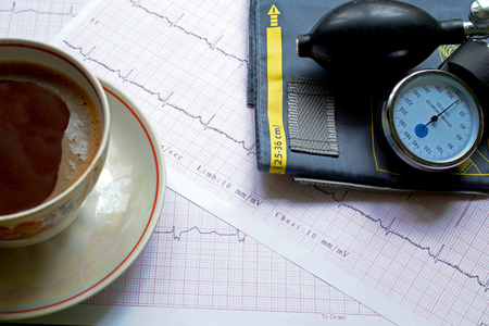 hypotension: Tonometer, cup of coffee, and ECG results on the table Stock Photo